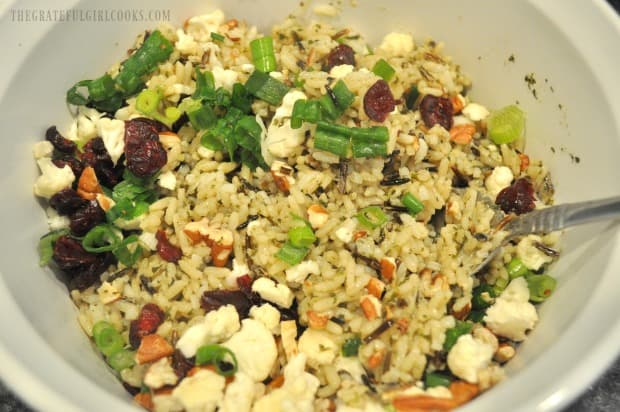 Wild rice, pecans, green onions, cranberries and cauliflower are combined in bowl.