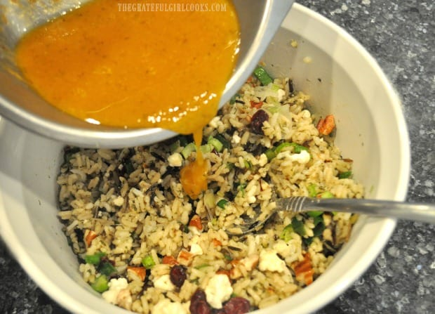 The pumpkin vinaigrette is poured over the wild rice salad, then stirred in.