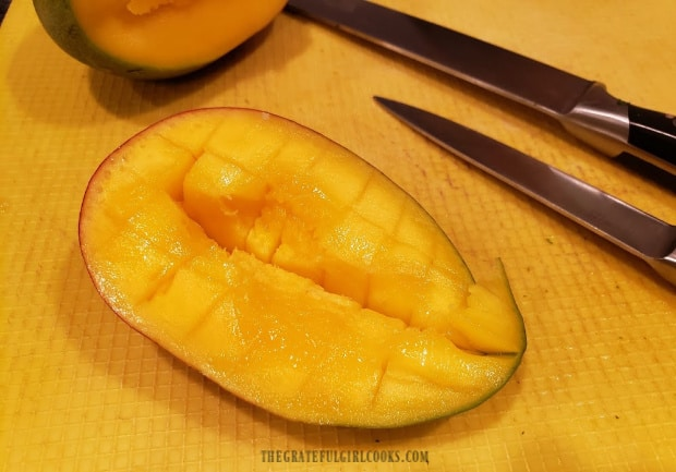 Mango is sliced into cubes before adding them to salsa.