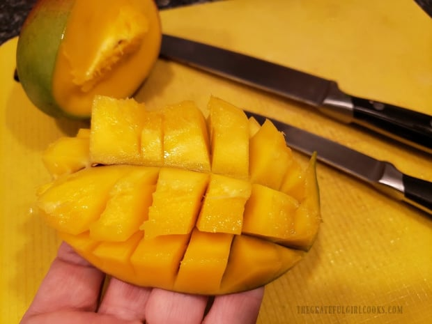 The mango is flipped to expose the cubes, and then they are cut away from the peel.