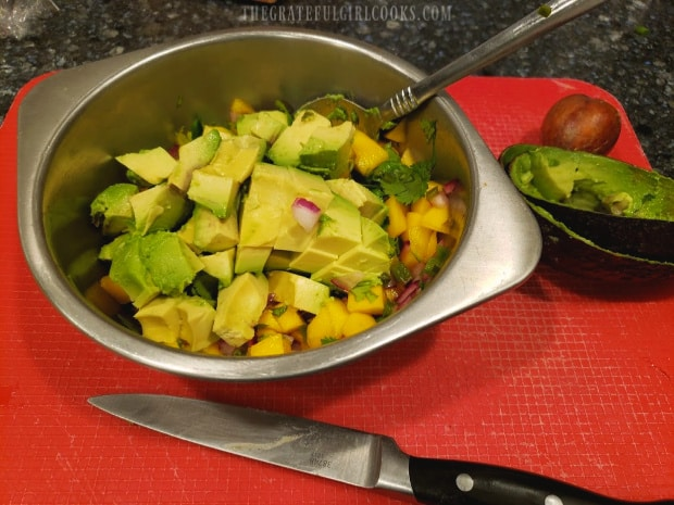 Ingredients for the mango avocado salsa are gently combined before serving.