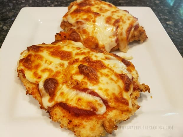Two pieces of air fryer chicken parmesan on a plate, ready to eat!
