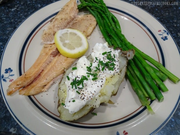 The grilled trout, on a plate with side veggies, ready to eat.