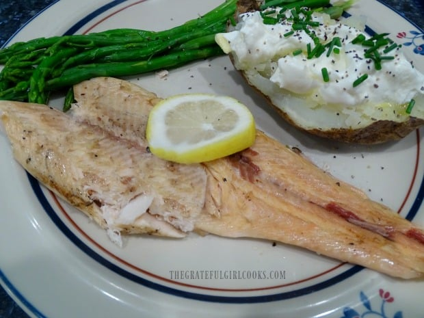 Garlic butter grilled trout fillet, served with a baked potato and asparagus.