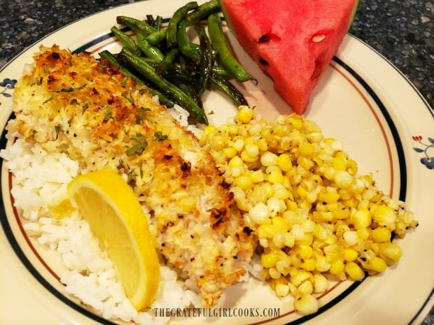Garlic parmesan rockfish fillet on rice, with green beans, corn, and watermelon on the side.