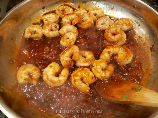 Asian sauce is added to the cooked shrimp, and heated through before serving.