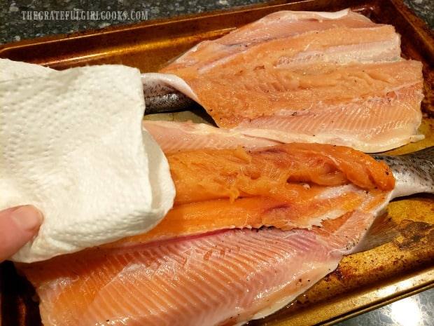Each trout is patted dry before putting it on the grill for smoking.