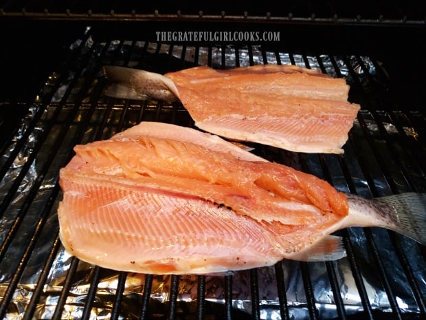 Traeger grill smoked trout is cooked skin side down on the grill.
