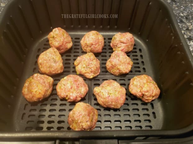 Air fryer Italian meatballs in the fryer, ready to be cooked.