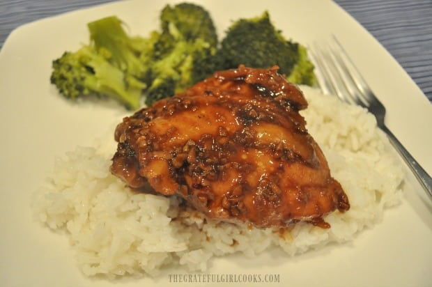 Chicken thigh with sauce is served on steamed rice, with broccoli on the side.
