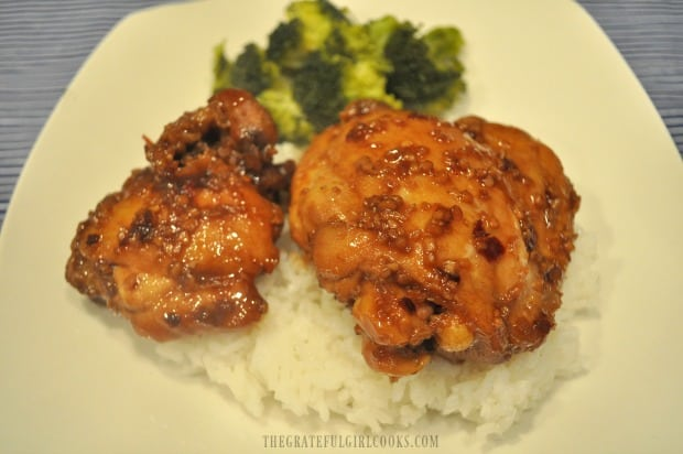 Finished Asian chicken thigh skillet dish is served on top of steamed rice.