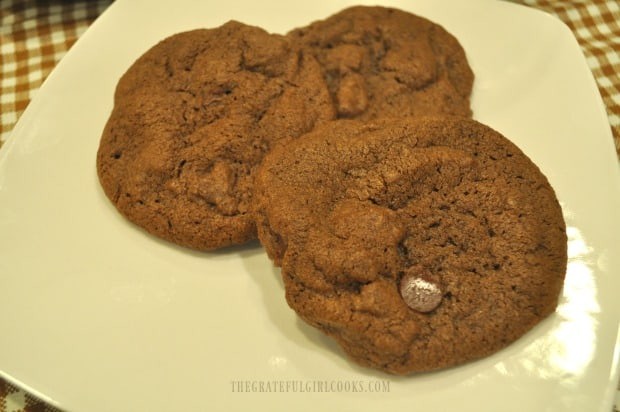 Three mocha chocolate chip cookies on a white plate.