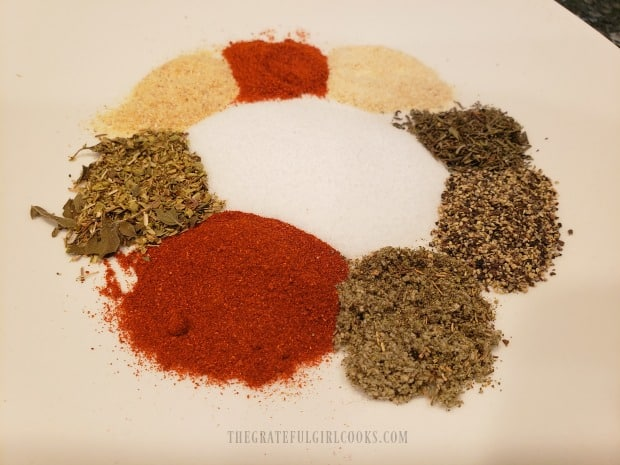 Poultry seasoning ingredients measured out on a white plate.