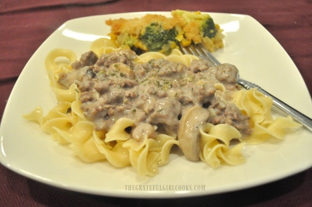 Hot, buttered egg noodles are topped with the ground beef stroganoff to serve.