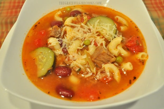 A bowl of hearty minestrone soup, topped with grated Parmesan cheese.