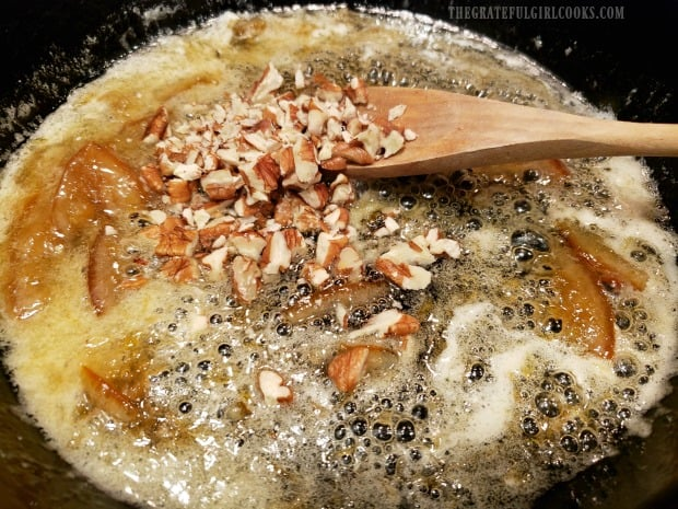 Chopped pecans are added to marmalade glaze in skillet.