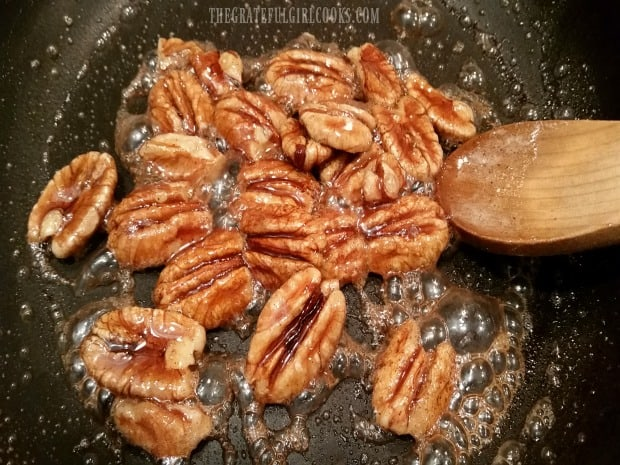 Pecan halves are cooked and candied with butter, cinnamon and brown sugar.