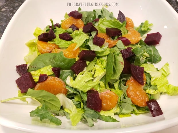 Spring greens in bowl are topped with chopped beets and mandarin oranges.