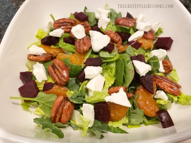 Candied pecans and crumbled goat cheese are added to the salad.