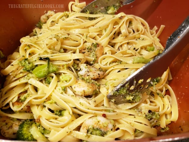 The herbed shrimp broccoli pasta is gently tossed before serving.