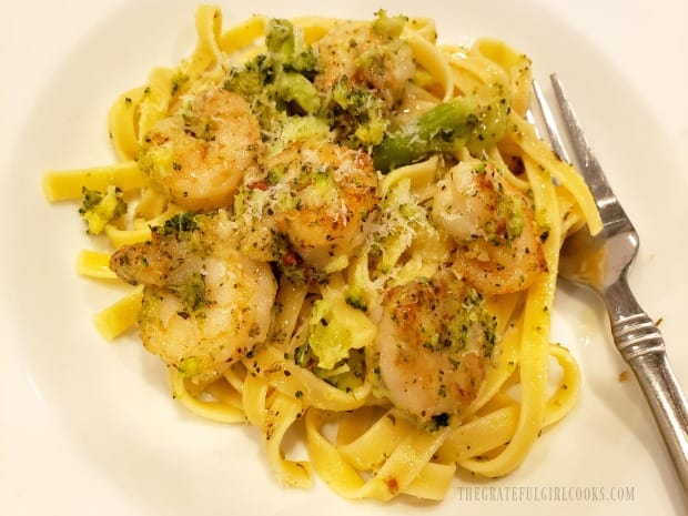 A close up of herbed shrimp broccoli pasta, with a fork on the side.