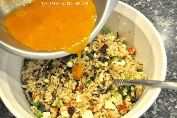 The finished pumpkin vinaigrette is poured over wild rice salad and then served.