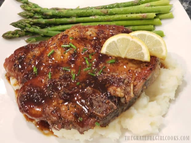 The brown sugar pork chops are served on mashed potatoes, with asparagus on the side.