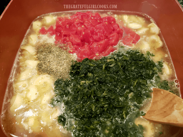 Drained spinach, tomatoes, and spices are added to the tortellini soup.