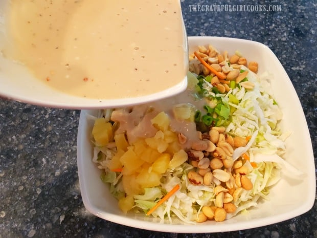The salad dressing is added to the bowl of pineapple peanut coleslaw.