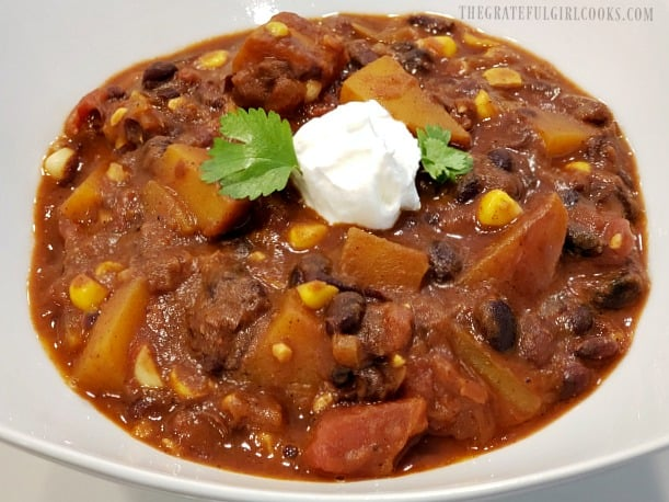 A bowl of black bean butternut squash chili garnished with cilantro and sour cream.