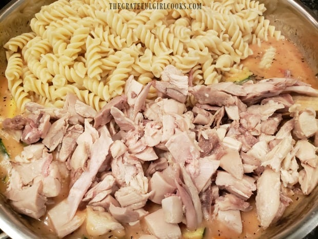 Cooked pasta and chicken are added to the creamy sauce.