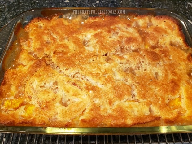 Fresh peach cobbler, straight from the oven, cooling on a wire rack.