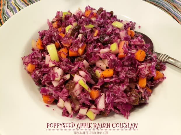Crisp Poppyseed Apple Raisin Coleslaw, w/ purple cabbage, carrots, Granny Smith apples, & raisins, is tossed with poppyseed dressing, and served cold.