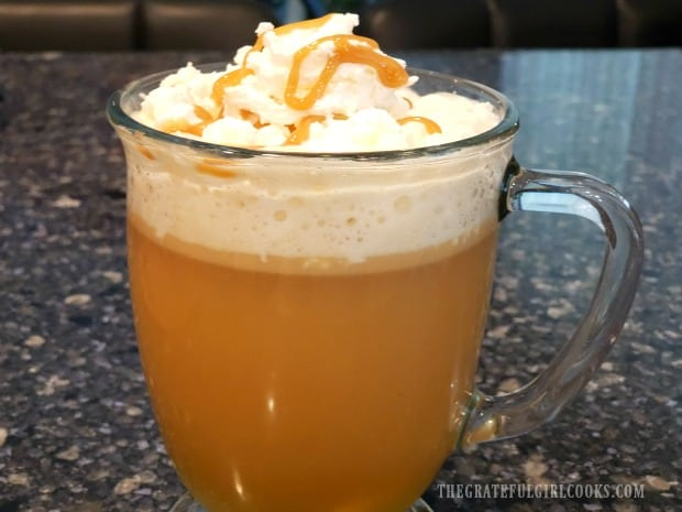 A mug of caramel apple cider, topped with whipped cream and caramel sauce.