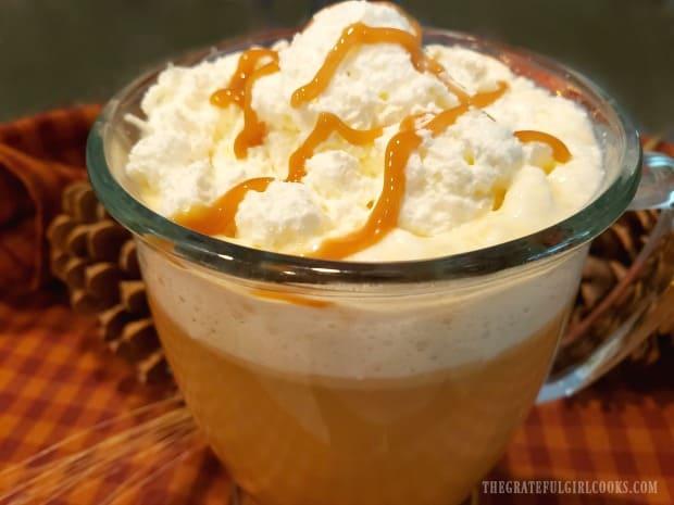 Whipped cream and caramel sauce top a mug of hot caramel apple cider.