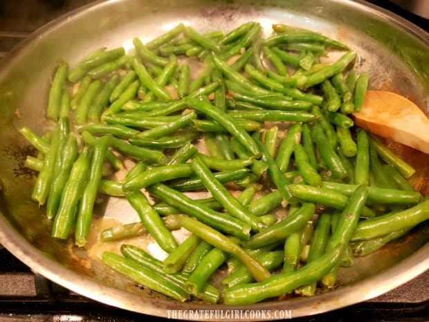The green beans are cooked about 10 minutes until broth has dissipated.
