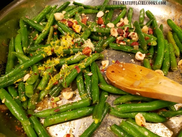 Minced garlic, chili flakes, lemon zest and hazelnuts are added to green beans.