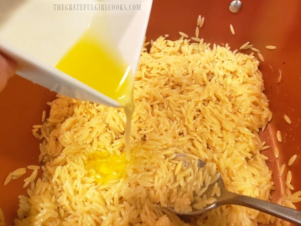 Melted butter is added to the cooked orzo.