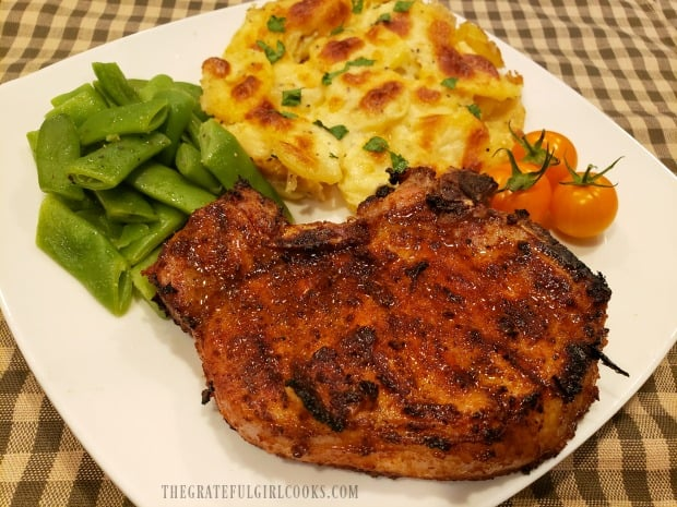 A plate with a pork chop, green beans, tomatoes and Scalloped Potatoes For Two.