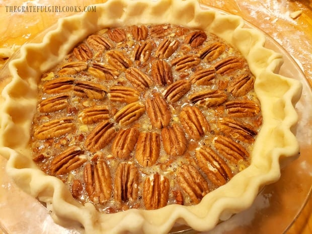 Pecans decorate the top of the pie before it is baked.