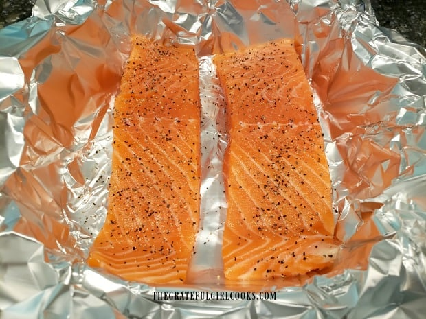 Skinless salmon fillets are lightly seasoned with salt and pepper.