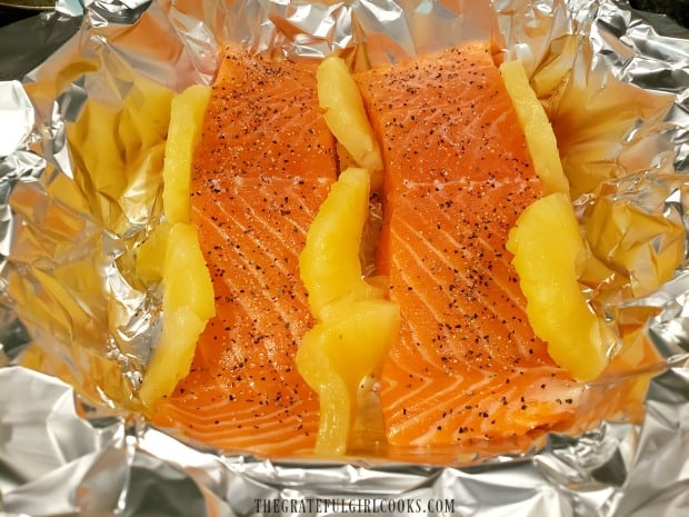 Pineapple rings (cut in half) are wedged around the salmon fillets in pan.