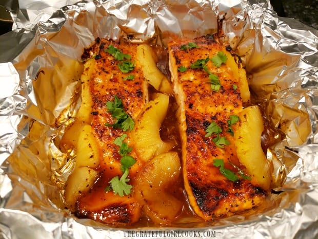 Baked then broiled salmon is garnished with chopped cilantro before serving.