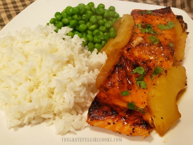 Sweet Spicy Salmon, served on a white plate with steamed rice and green peas.