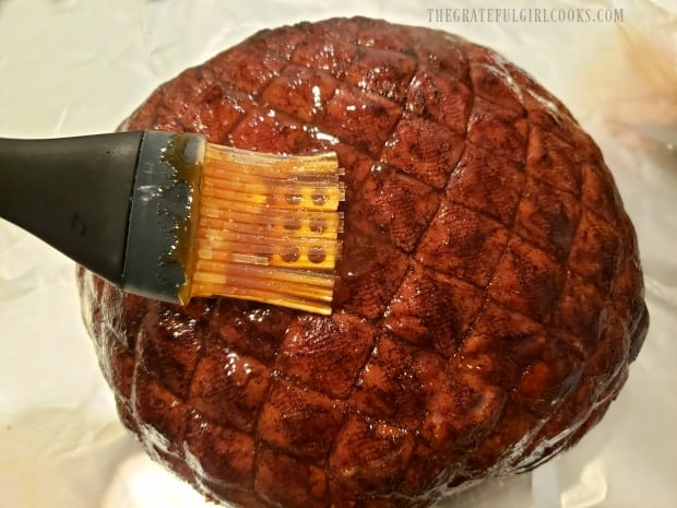 A ham is place on aluminum foil, then coated with brown sugar glaze.