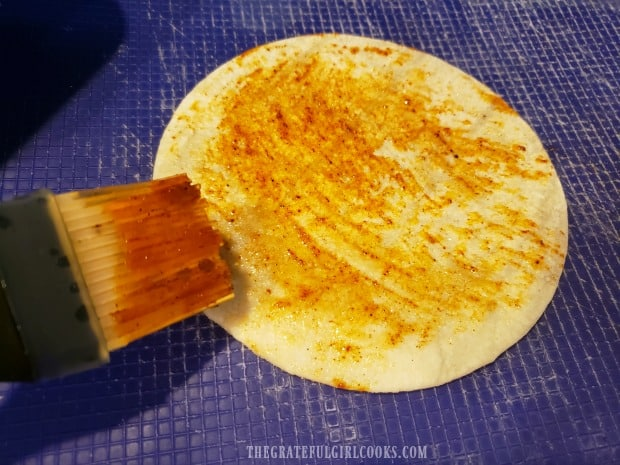 Each corn tortilla is brushed with the spicy sauce before cooking.