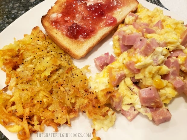 Crispy homemade hash browns, served with scrambled eggs, ham, and toast.
