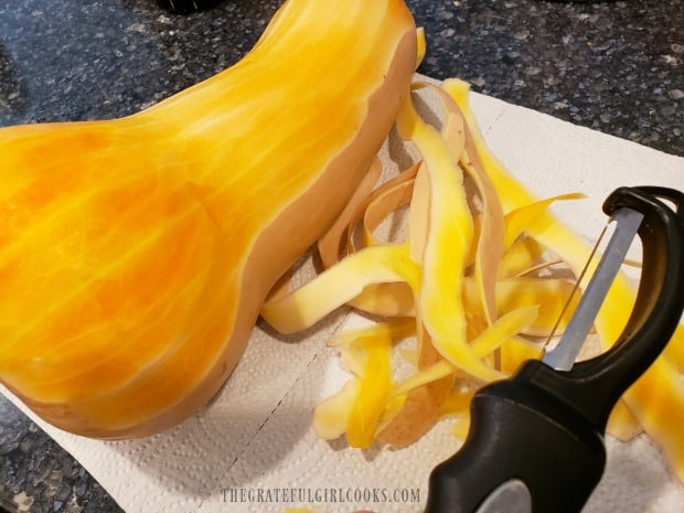 A vegetable peeler is used to peel the butternut squash.