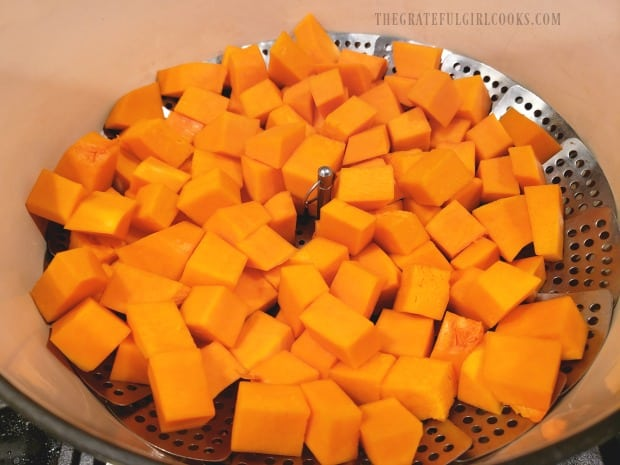 The squash cubes are cooked in steamer in a pan over boiling water