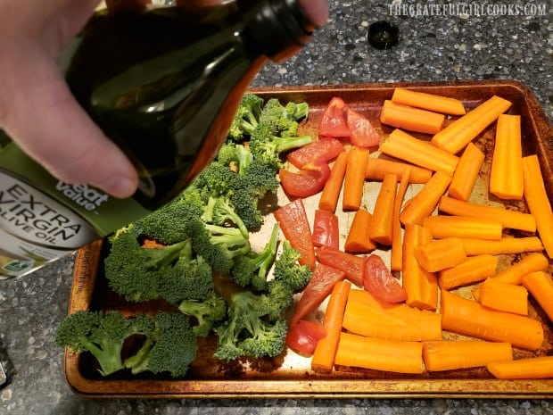 The vegetables are drizzled with olive oil before seasoning.